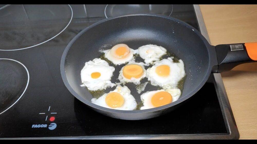 Los huevos fritos se rompen en una olla caliente que contiene una fina capa de grasa de cocción.